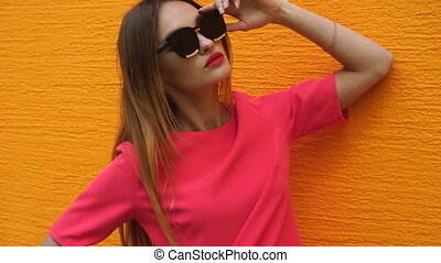 adorable young blonde lady in red suit and black sunglasses posing