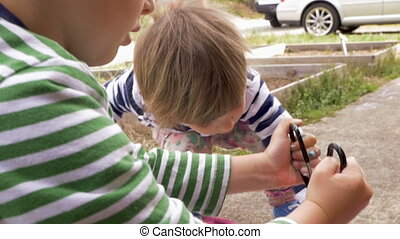 Adorable young boy and girl making colorful arts and crafts project outside