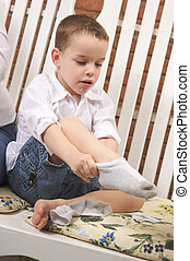 Adorable Young Boy Getting Dressed Putting His Socks On