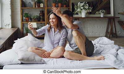 Adorable young couple is making video call with smartphone,...