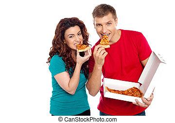 Adorable young couple relishing yummy pizza