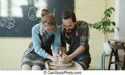Adorable young couple working with clay on pottery wheel ...
