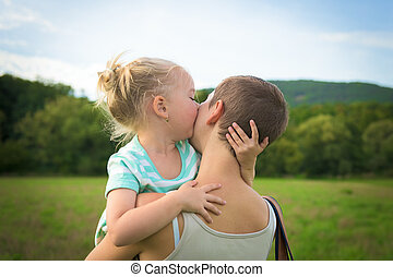 Adorable young girl kissing her mother