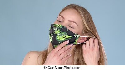 Adorable young girl taking off her face mask against viruses...
