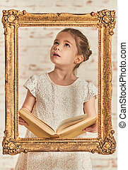 Adorable young little girl reading a book