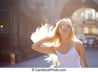 Adorable young model with long hair wearing glasses, posing at the passage in rays of sun. Copy space