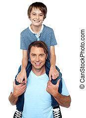 Adorable young son enjoying piggyback ride