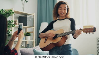 Adorable young woman amateur guitarist is playing the guitar...