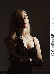 Adorable  young woman with long hair in black corset and silk gloves posing in the dark