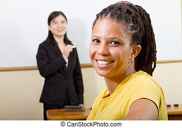 adult african female student in classroom, background is her...