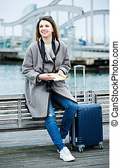 woman with luggage posing at quay and smiling