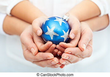 Adult and child hands holding christmas bauble together