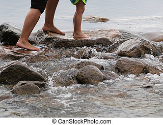 Adult and children's feet on rocks - Bare feet of an adult ...