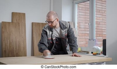 adult bald worker man is grinding wooden board by hand...