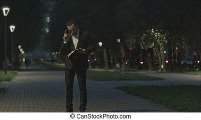 Adult bearded business man talking on cell phone while standing in the city street, business man have conversation, stylish hipster in suit using cellphone