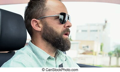 Adult bearded man in sunglasses driving the car. Young hipster drives a car and talks to a fellow traveler. Business man drives a vehicle.