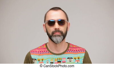 Adult bearded man in sunglasses posing