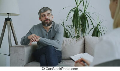 Adult bearded man sitting on couch talking to female...
