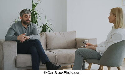 Adult bearded man talking about his problems to psychologist...