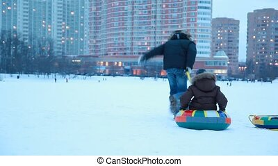 Adult boy is pulling sled fast with other boy in winter