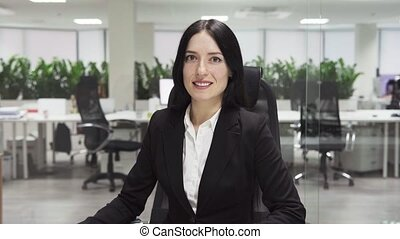 Adult business woman smiling at workplace in office