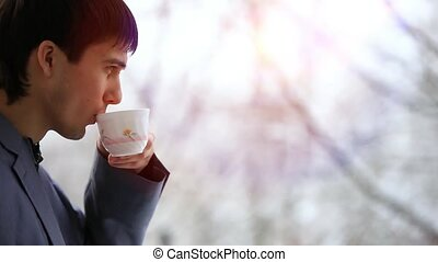Adult businessman relaxing and drinking a cup of tea, looking out Of window. It snows outside. HD. 1920x1080
