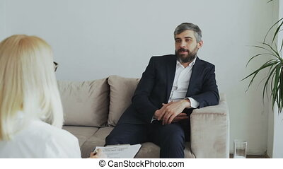 Adult businessman sitting on couch talking to female psychotherapist in office