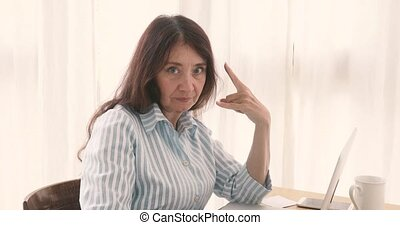 Adult businesswoman showing rock and roll gesture - Serious...