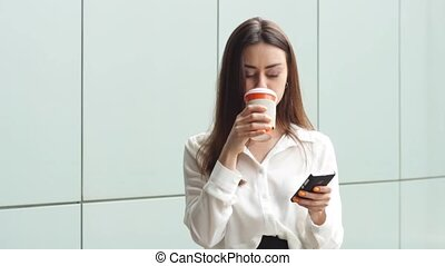 Adult businesswoman with hot drink using smartphone -...