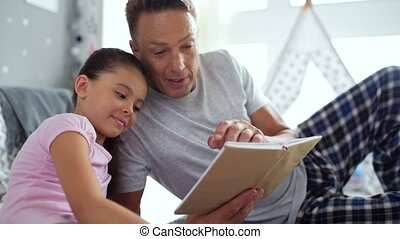 Adult caring man reading a book for his little daughter