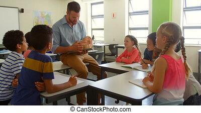 Adult Caucasian male teacher explaining anatomical model in ...