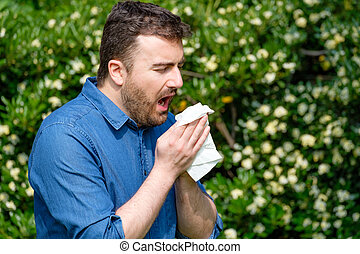 Adult caucasian man sneezes because of an allergy.
