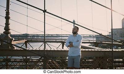 Adult Caucasian man standing at Brooklyn Bridge waiting for...