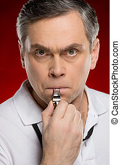 adult coach man blowing into whistle. closeup of judge portrait standing on red background
