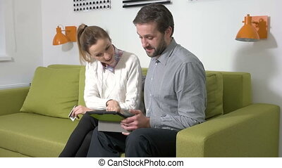 Adult couple at home doing online shopping with tablet.