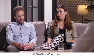 Closeup of bored yawning man listening to accusations of wife while sitting on meeting with family therapist. Woman drinking water to calm down and explaining problems in family to marriage counselor