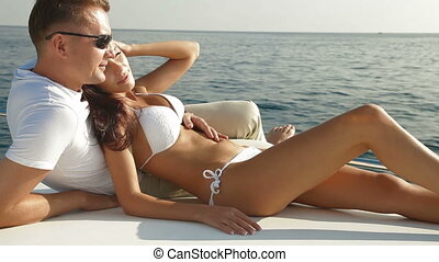 Adult couple enjoying summer vacation on deck of yacht in Mediterranean sea
