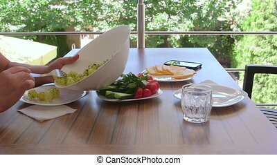 Adult couple having dinner on balcony with patio in summer day
