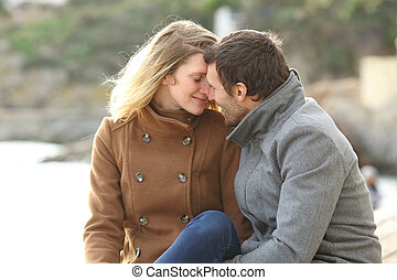 Adult couple in love flirting on the beach in winter