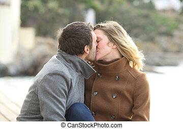 Adult couple in love kissing on the beach in winter