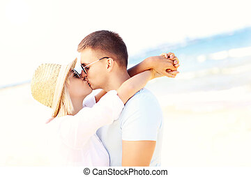 Adult couple kissing at the beach
