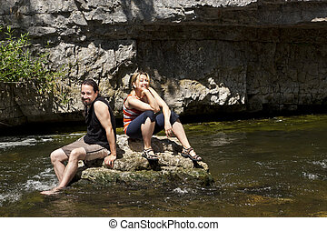 Couple relaxing on a rock in the river