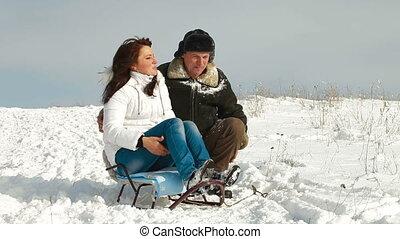 couple sitting on sledge