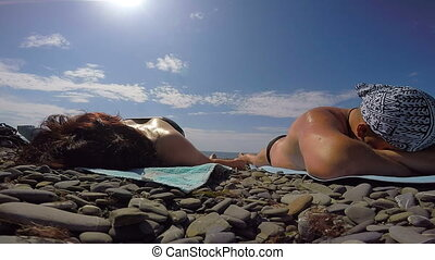 Adult couple spends summer vacation relaxing tanning lying...