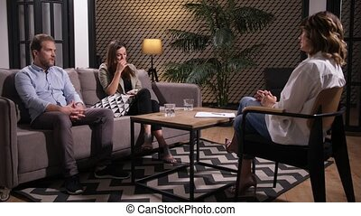 Unhappy husband and wife trying to solve relationship problems with support of family consultant, woman crying and wiping away tears with napkin. Conflicting couple seeking help of marriage counselor