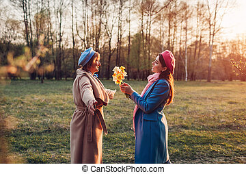 Adult daughter giving flowers as present to her senior mother in spring park. Mother's day concept. Family values