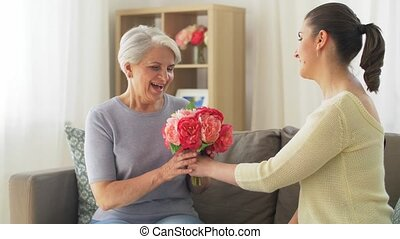adult daughter giving flowers to old mother - family, mother...
