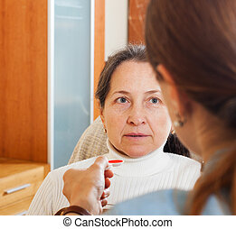 daughter giving the cough syrup to mature mother