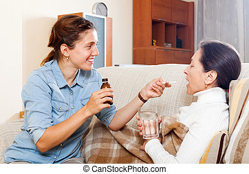 Adult daughter giving the liquid medicament to mother -...