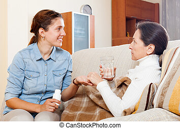daughter giving the medicament to mature mother